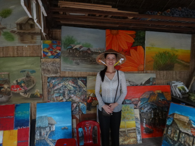 A woman selling her husband's paintings of the Mekong Delta
