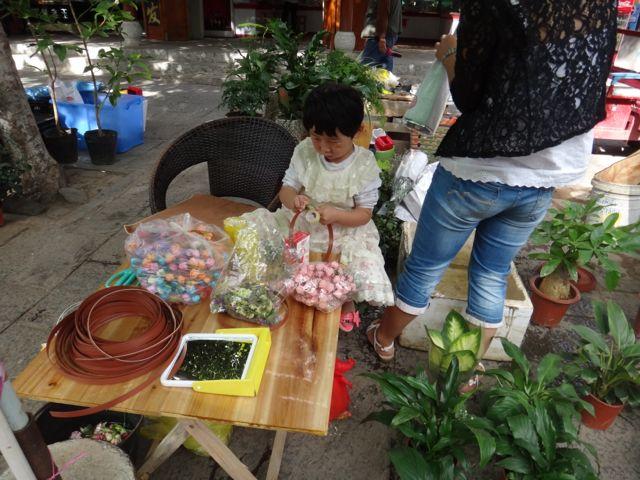 A little girl making flower wreathes
